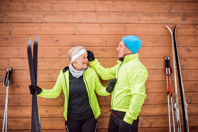 Active senior couple getting ready for cross-country skiing. Winter time.